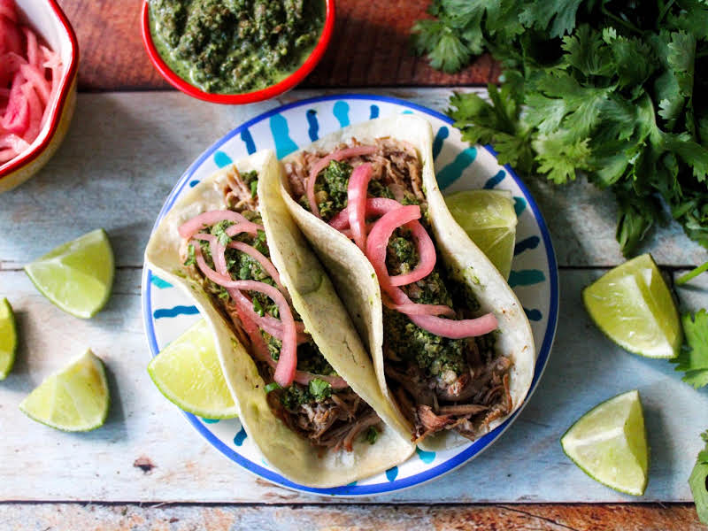 Pulled pork tacos with pickled red onions, cilantro pesto and pumpkin seeds